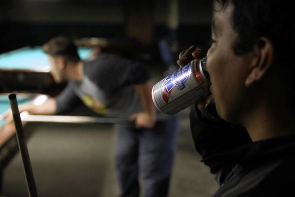 Demetri Kats, left, lines up a shot while his friend Oscar Prada enjoys a beer at Chris's Billiards, one of the many Chicago BYOB businesses that let people bring in their own alcohol.