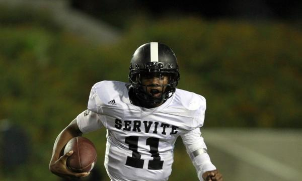 Servite quarterback Travis Waller runs the ball during a game against Edison last month. Servite moves up one spot in this week's rankings following its win Friday over Santa Margarita.