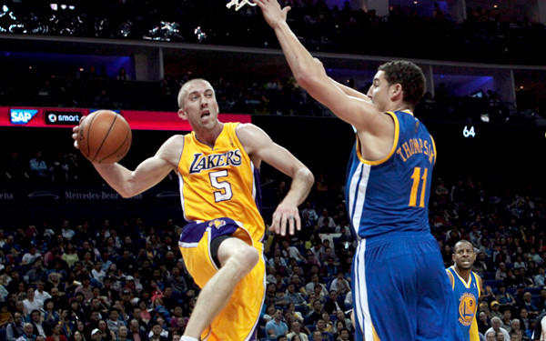 Veteran Steve Blake, elevating for a pass around Warriors guard Klay Thompson, is one of three Lakers averaging four assists a game in the preseason.