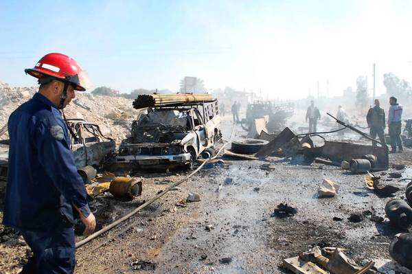 Firemen work at the site of a car bombing in Hama, Syria.