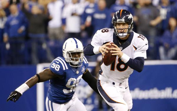 Broncos quarterback Peyton Manning evades Colts outside linebacker Robert Mathis.
