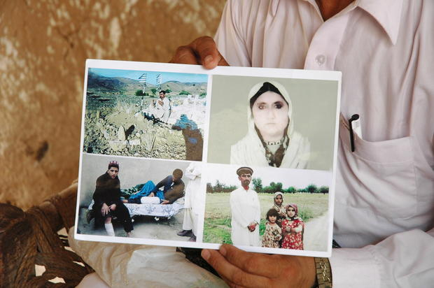 Rafeequl Rehman holds pictures of his late mother, Mamana Bibi, her grave and his children. Bibi was killed and the children injured in a U.S. drone strike last year while picking vegetables in the family fields in North Waziristan, Pakistan, Amnesty International reports.