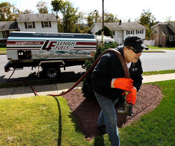 Driver Paul Darby, with Lehigh Fuels, delivers heating oil to a home on Sumner Avenue in Whitehall Friday.