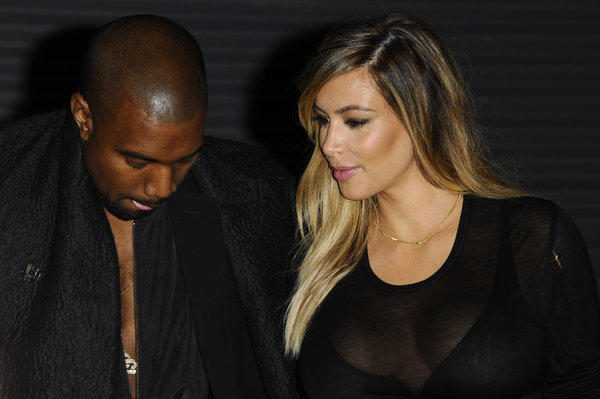 Kanye West, left, and Kim Kardashian, at Givenchy's ready-to-wear fashion show last month in Paris, sometimes use clothes to stay close.