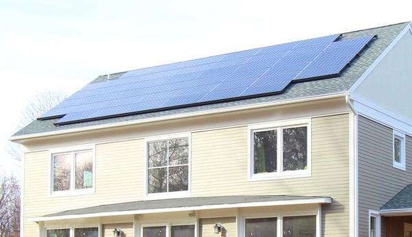Solar panels line the roof on the back side of this Harwinton home.