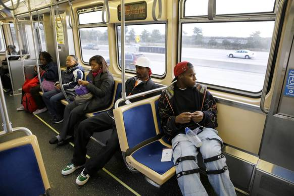 Martes Carr, 25, right, rides the CTA red line south on the first weekday that the CTA's Red Line is open for business after being closed for a five-month reconstruction.