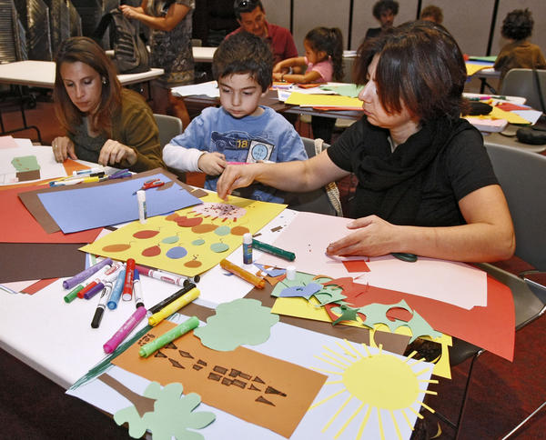 Left to right making collages are Sandy Gililand, Arno Asatryan, 6, and his mother Arus Sargsyan at the It's Big! Draw together Glendale event at the Central Library in Glendale on Saturday, Oct. 19, 2013. Children and adults made collages from construction paper and pasted these on a large and long piece of butcher paper that will be displayed at the library.