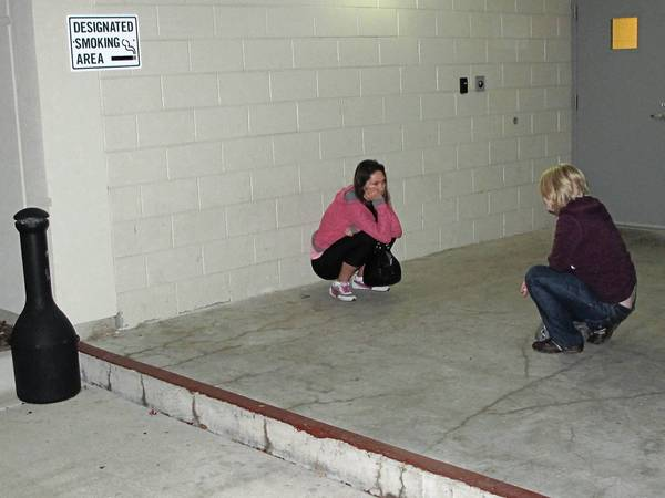 Two students take a break from class as one student smokes in the designated smoking area outside the D Building at Moraine Valley Community College.