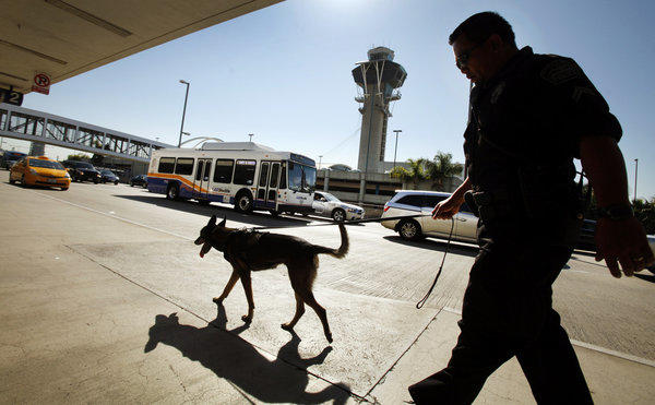 A Los Angeles Airport police officer and a bomb-sniffing dog walk through Los Angeles International Terminal 2 on Oct. 15, as part of the increased security at the airport following a rash of dry-ice bombs.