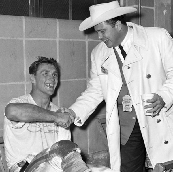 "In this 1960 photo, Kenneth Stanley ""Bud"" Adams, right, shakes hands with the Houston Oilers' Billy Cannon in the dressing room in Houston. Adams died of natural causes in his Houston home, the Tennessee Titans announced Monday. He was 90."