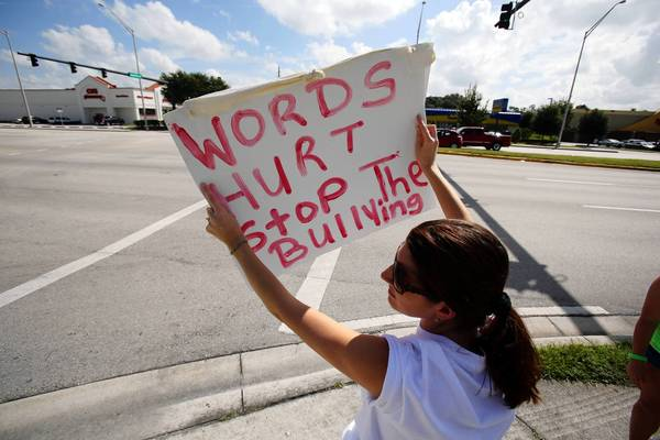 Aimee Galassi holds a sign during a carwash fundraiser for bullying victim Rebecca Ann Sedwick at a 7-Eleven in Lakeland, Fla. on Sept. 15. Rebecca jumped to her death from a silo at a cement factory. She had been bullied.