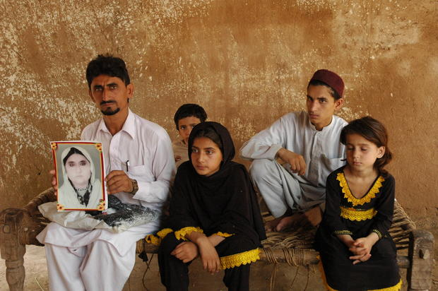 "Rafeequl Rehman sits with his children, holding a photograph of his mother, Mamana Bibi, who  he says was killed in a U.S. drone strike in Pakistan last year.  ""If I get some money I will get a lawyer and fight for my right to get justice from the world,"" Rehman told Amnesty International. ""I am waiting for my justice."""