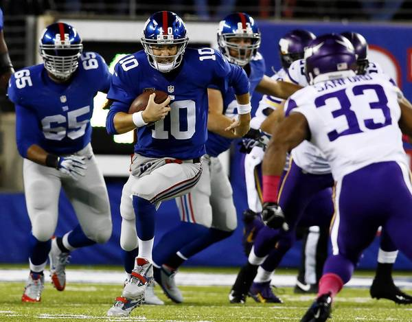 Giants quarterback Eli Manning (10) scrambles for a first down against the Vikings on Monday night. The game ended too late for this edition.