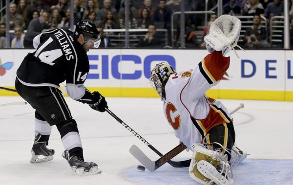 Calgary Flames goalie Karri Ramo, right, makes a save on Kings right wing Justin Williams during the first period of the Kings' 3-2 loss Monday.