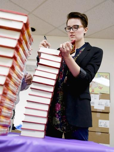 """young adult author Veronica Roth signs over 3,000 books at the Anderson and Sons warehouse, including her newest, """"Allegiant."""""""