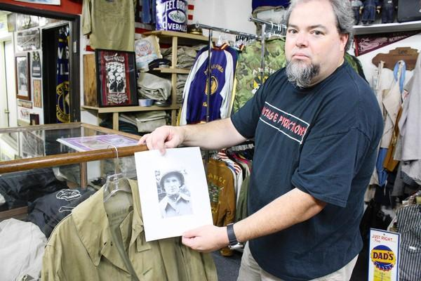Bob Chatt holds a photo of Ernie Pyle wearing the very same rain coat he just acquired for his collection.