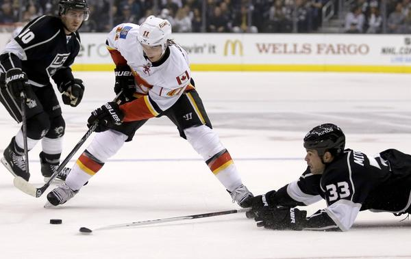 Kings defenseman Willie Mitchell, right, knocks the puck away from Calgary center Mikael Backlund as Mike Richards looks on Monday night.