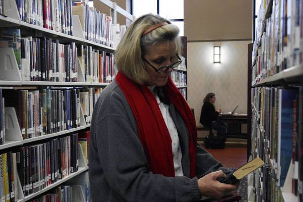 Glenview resident Barbara Carolan browses the shelves at the Glenview Public Library. Library officials report a rise in circulation and attendance numbers and may consider increasing their property tax levy in future years.