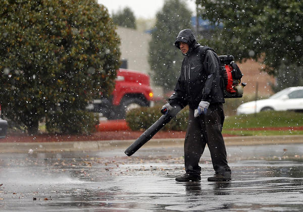 As snow falls, Jose Velez blows leaves in a parking lot in Yorkville.