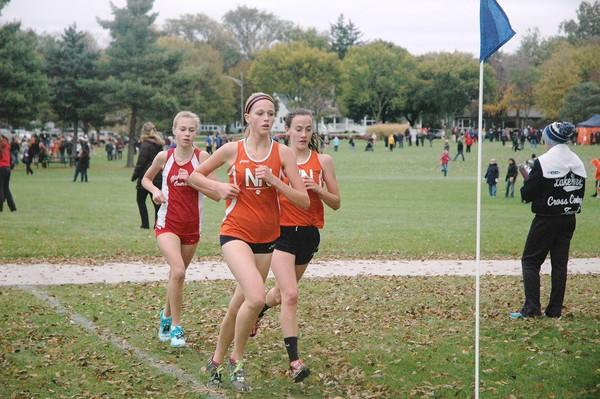 Naperville North's Elly DeTurris (center) and Kate Shannon (right) lead Naperville Central's Katie Hoffman at the DVC Championship meet on Friday.