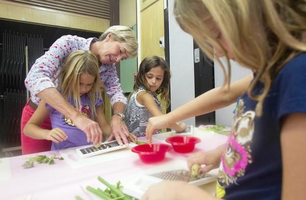 Laguna Beach school board member Ketta Brown helps Ruby Carter, 7, grate ginger as Julieta Comesana, 7, right, looks on during an after-school cooking class at Top of the World Elementary School on Monday.