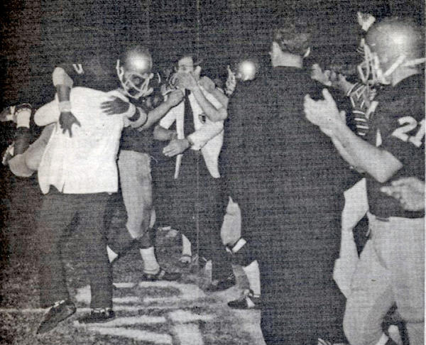 Coach Jack Friedman, at left with his back to the camera, hugs a St. Francis football player after the Golden Knights shut out Temple City in an October 1973 game. The Rams had not lost a game since 1969 and had been hoping to set a state record of 47 consecutive wins.