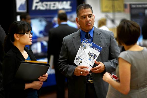 The unemployment rate last month dropped a notch, to a five-year low of 7.2%, but that was partly the result of workers leaving the labor market. Above, Melinda Walker, left, and Tomas Kringel listen to Angelina Tennis, who is recruiting workers at First Command Financial Services during a career fair in Miami.