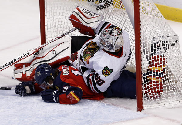 Panthers center Jonathan Huberdeau crashes into Hawks goalie Corey Crawford