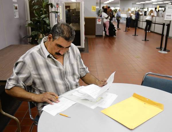 California's new jobless benefits software delayed checks for hundreds of thousands. Above, Luis Rodriguez, who has been out of work for a year, fills out forms at the Employment Development Department office in Sacramento.