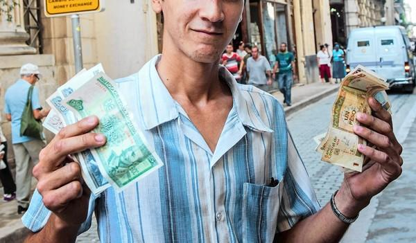 A Cuban displays Cuban pesos, left, and the more valuable convertible pesos Tuesday in Havana. Raul Castro's government announced that the dual-currency system will be changed.