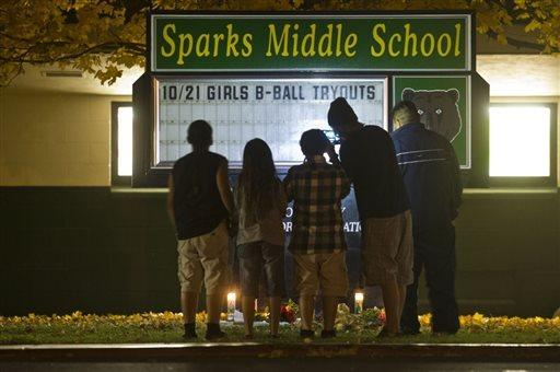 Children and parents gather at a makeshift memorial for slain teacher Michael Landsberry at Sparks Middle School in Nevada.