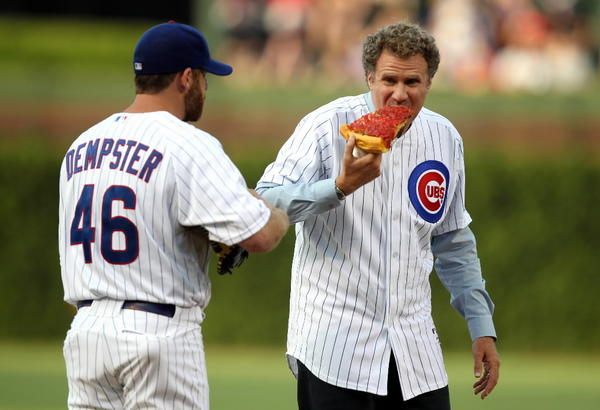 Actor Will Ferrell (right) eats pizza beside Cubs pitcher Ryan Dempster (left) before throwing out the first pitch at the Cubs-Miami Marlins game at Wrigley Field July 18, 2012.