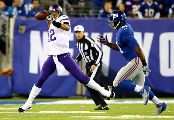 Vikings quarterback Josh Freeman scrambles as Giants defensive end Justin Tuck closes in.