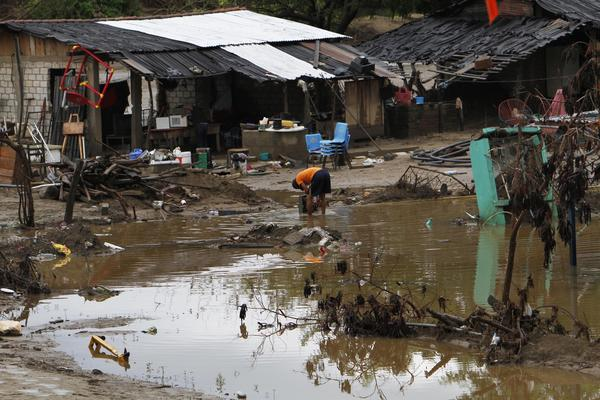 A resident whose home was flooded rinses away mud from his TV in Coyuca de Benitez, near Acapulco, on Wednesday. Raymond weakened from a hurricane to a tropical storm Wednesday and began moving away from Mexico's Pacific coast.