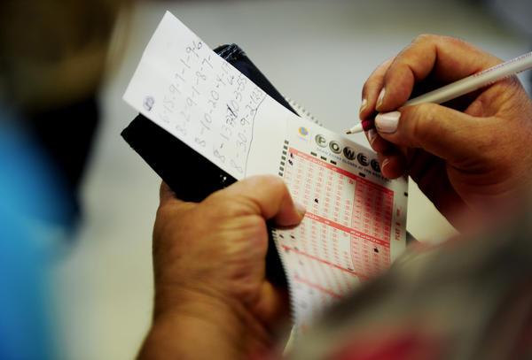 A woman fills out her Powerball ticket inside Bluebird Liquor in Hawthorne.