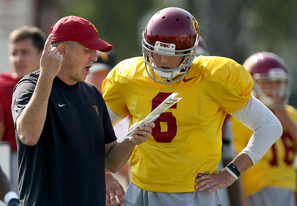 USC offensive coordinator Clay Helton works with quarterback Cody Kessler during a practice at USC. The two are hoping to cut down penalties in the game against Utah on Saturday.