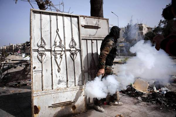 A fighter with the Free Syrian Army throws a homemade smoke bomb to blind government soldiers in Aleppo. With informants a major concern to both sides in the conflict, FSA leaders have created their own intelligence branch to weed out spies and to recruit them.