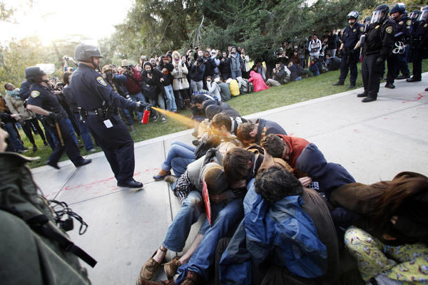 UC Davis police officer John Pike uses pepper spray on campus demonstrators.