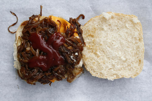 A cheeseburger with onions is seen at a snack trailer along the A49 near Tittensor, central England August 20, 2013.
