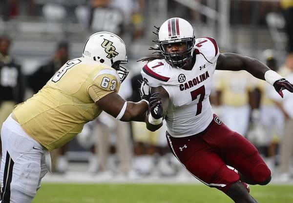 Knights offensive lineman Jordan McCray blocks South Carolina defensive end Jadeveon Clowney during their teams' match at Bright House Networks Stadium.