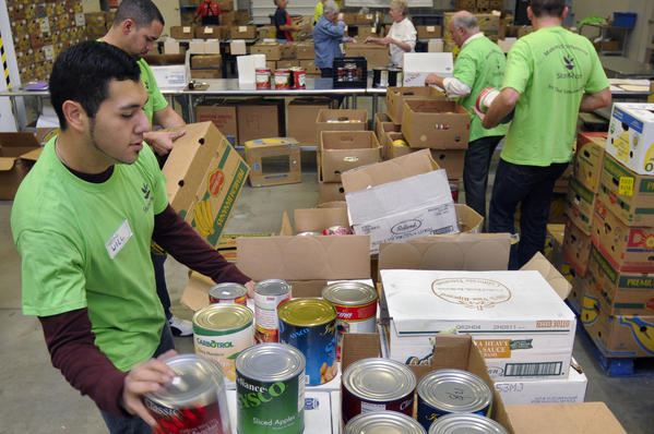 William Jara, of Manchester, (left) sorts salvageable canned goods to be distributed to anti-hunger agencies in the enlarged volunteer work area at Foodshare in Bloomfield Wednesday.
