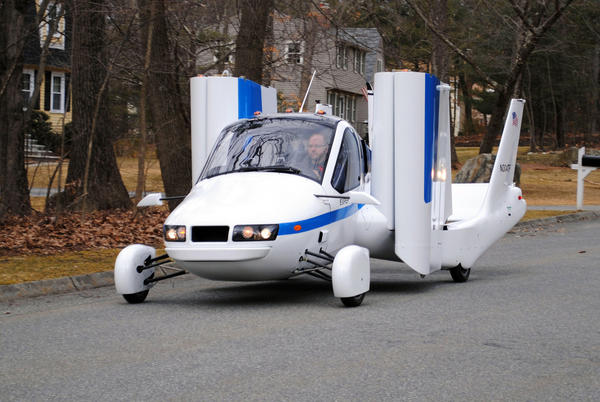 "Terrafugia Inc.'s prototype flying car, dubbed the Transition, travels down a street with its wings folded. Crowdfunding is attractive to start-ups such as Terrafugia, says the company's co-founder, Carl Dietrich. ""For publicly traded companies, individual investors don't have the ability to influence the success and failure of a company,"" Dietrich said. ""But for small start-ups, they absolutely have the ability to influence success and failure. That's exciting and something we haven't seen before."""