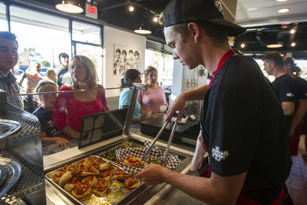 Jack Platner fills an order for pepperoni pin wheels during the grand reopening of Sgt. Pepperoni's Pizza Store on Friday.