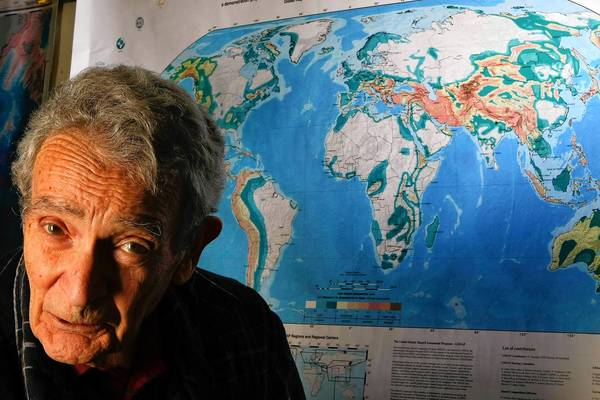 Vladimir Keilis–Borok on the UCLA campus in 2011, next to a map showing the Earth's key fault lines.