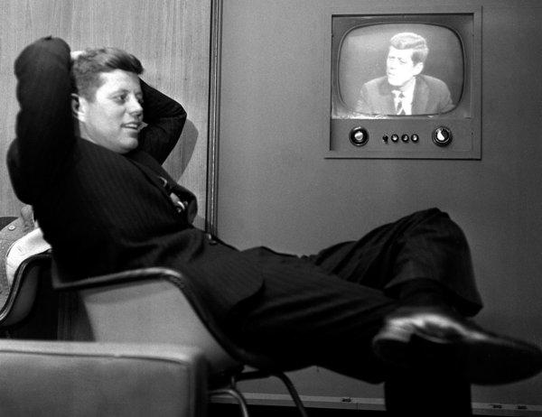 Sen. John F. Kennedy sits next to a playback of his televised appearance in Milwaukee for the Wisconsin presidential primary two days later.