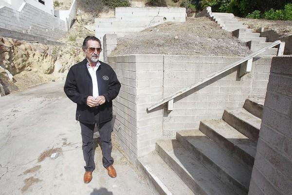 Local architect Morris Skenderian stands on one of the last properties that remain undeveloped and a reminder of the 1993 firestorm. Skenderian helped many people design new homes after the 1993 Laguna Beach fire.