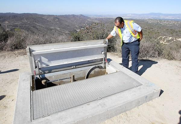 Laguna Beach County Water District pump station manager Ramon Calderon opens the city's 3-million gallon reservoir station at Top of the World that was built after the 1993 fire.