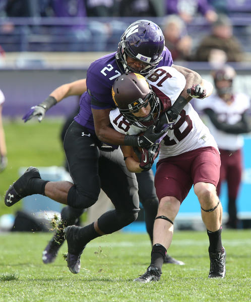 Northwestern's Matthew Harris tackles Minnesota's Derrick Engel in the third quarter.