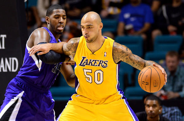 Lakers center Robert Sacre works in the post against Kings power forward Jason Thompson during a preseason game.