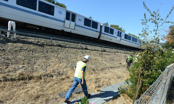 An investigator walks along tracks during a reenactment of Saturday's accident that killed two BART workers.